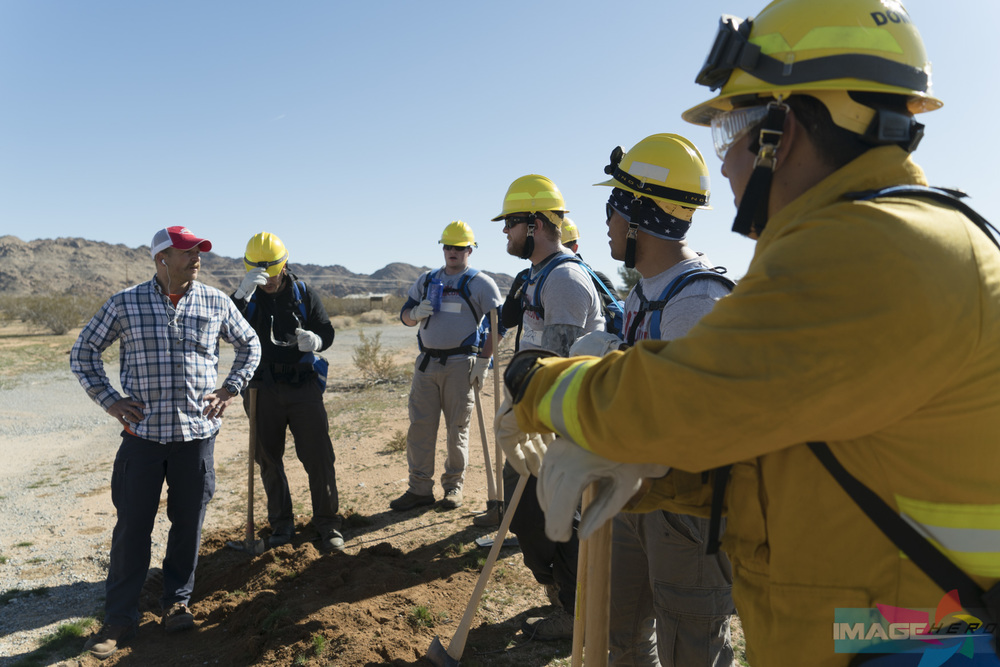 Team Rubicon Wildland Instructor Ben Oakleaf (left) debriefs the team on how well they did setting up a barrier on a fireline during a field training exercise for Fire Fighter Type 2.