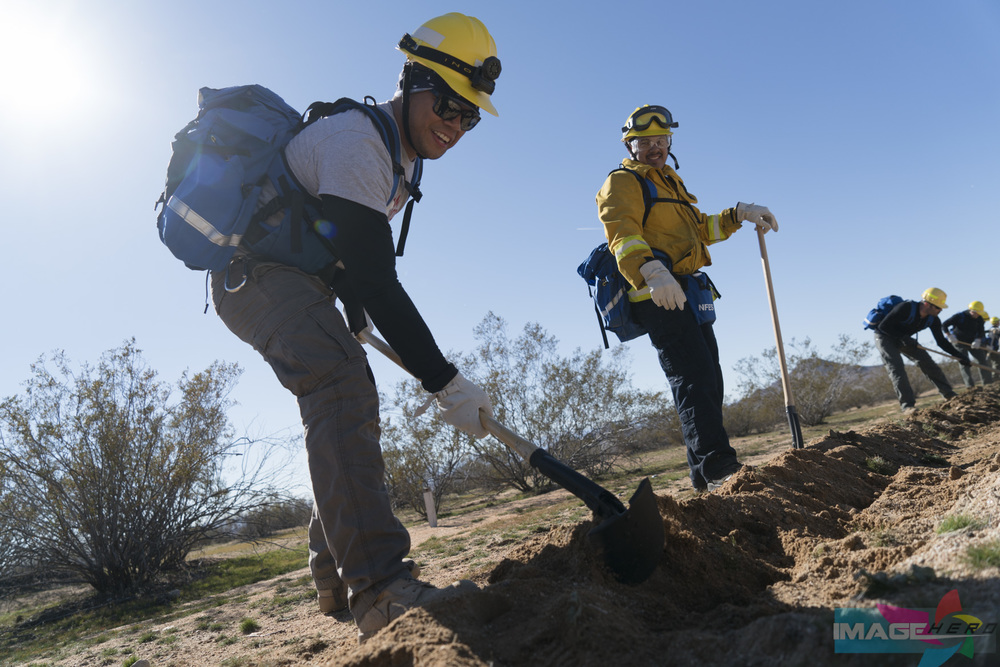 Team Rubicon members Charles Aquino (left) and Dominick Sanchez use hand tools to improve a barrier on a fireline during a field training exercise for Fire Fighter Type 2.