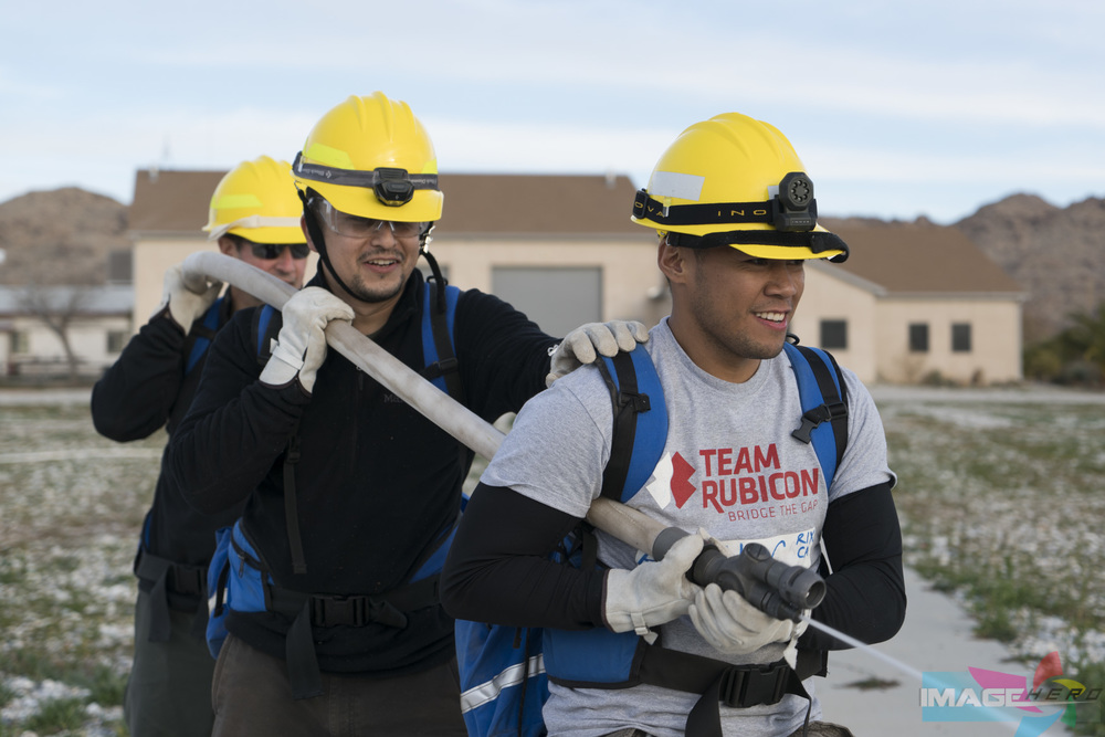 Team Rubicon members (right to left) Charles Aquino, Jonathan Quinones, and Kevin Mollenhauer work together to man a fire hose during a field training exercise for Fire Fighter Type 2.