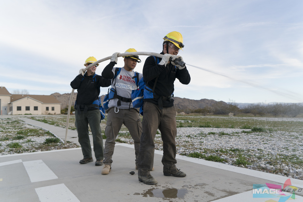 Team Rubicon members (right to left) Jonathan Quinones, Charles Aquino, and Kevin Mollenhauer work together to man a fire hose during a field training exercise for Fire Fighter Type 2.