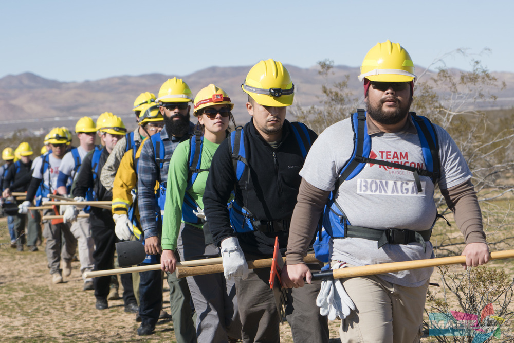 Team Rubicon members from FFT2 (Fire Fighter Type 2 Training) march in a single file line toward their first exercise.