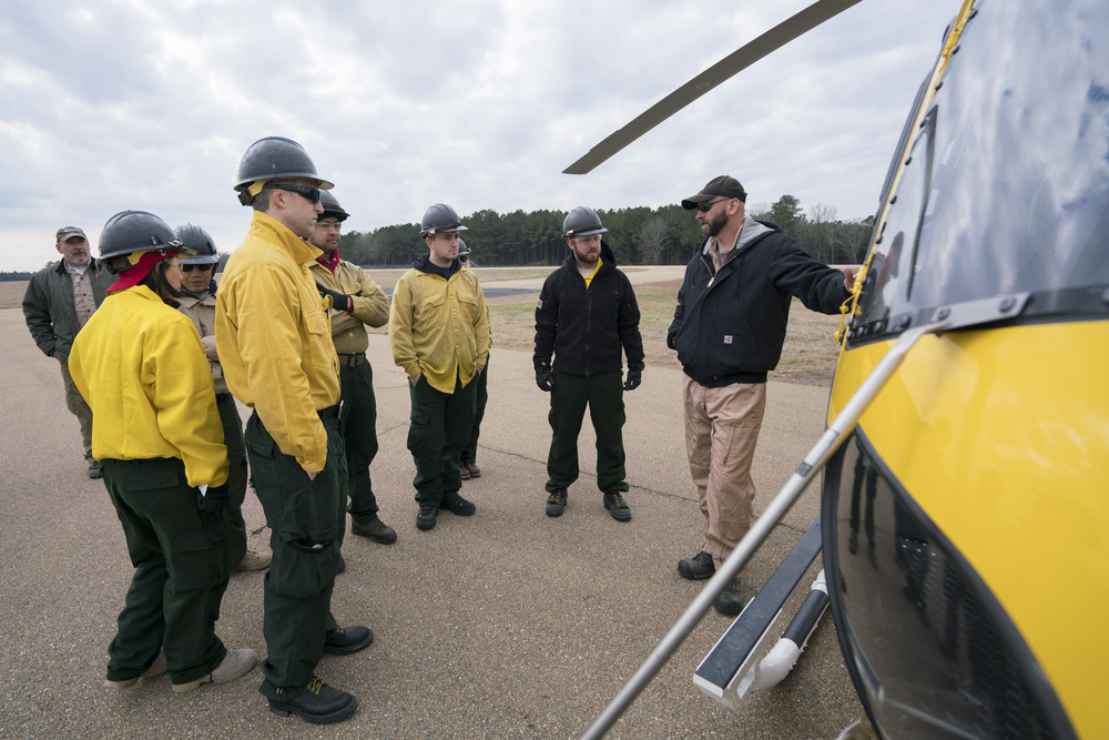 Pilot Preson Aro, right, teaches Team Rubicon wildland firefighters the functions and capabilities for a type-3 helicopter. Team Rubicon, with a partnership with the Bureau of Land Management, are being trained to become helicopter crewmembers for helitack teams to combat forest fires.  This is the first cohort to go to through this specialize training tailored for Team Rubicon volunteers.