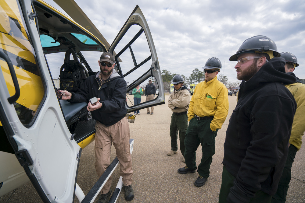 Pilot Preson Aro, left, teaches Team Rubicon wildland firefighters the functions and capabilities for a type-3 helicopter. Team Rubicon, with a partnership with the Bureau of Land Management, are being trained to become helicopter crewmembers for helitack teams to combat forest fires.  This is the first cohort to go to through this specialize training tailored for Team Rubicon volunteers.