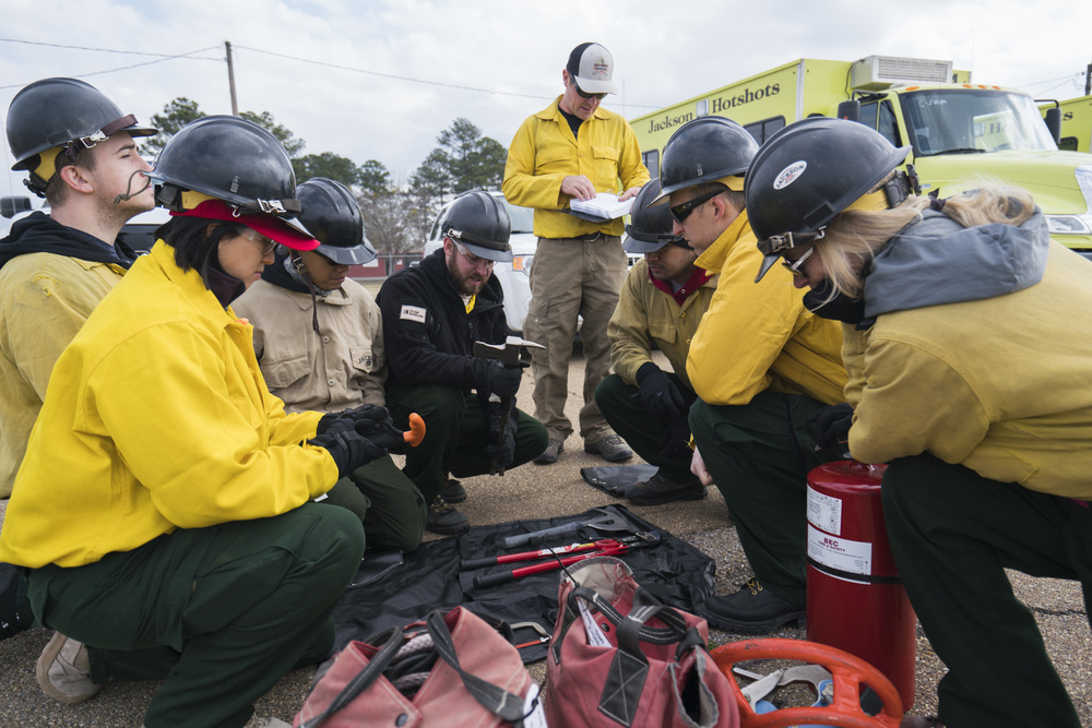 Team Rubicon wildland firefighters look at a crash kit to see what tools are inside. Team Rubicon, with a partnership with the Bureau of Land Management, are being trained to become helicopter crewmembers for helitack teams to combat forest fires.  This is the first cohort to go to through this specialize training tailored for Team Rubicon volunteers.