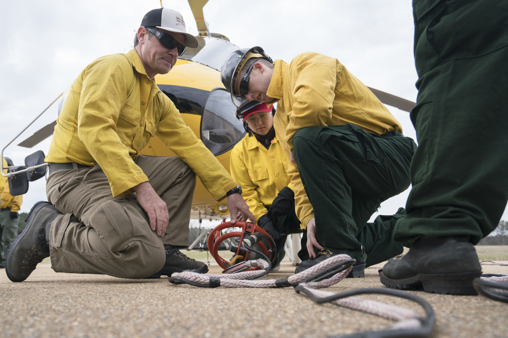 Jason Notz, left, shows how a long-line attaches to a hook. Team Rubicon, with a partnership with the Bureau of Land Management, are being trained to become helicopter crewmembers for helitack teams to combat forest fires.  This is the first cohort to go to through this specialize training tailored for Team Rubicon volunteers.