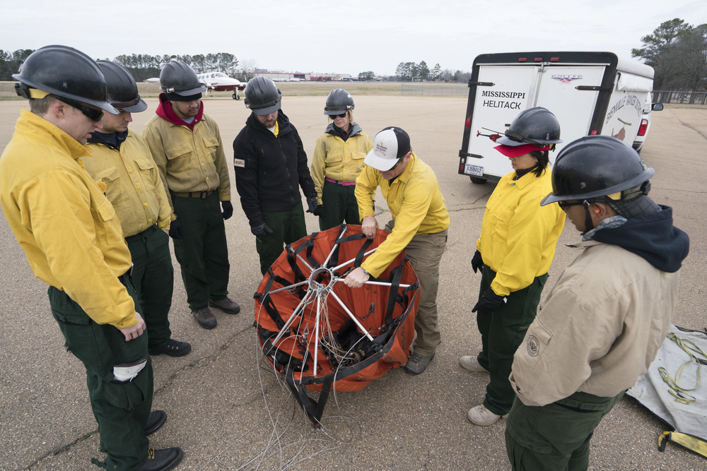 Jason Notz, center, show how to deploy a water bucket. Team Rubicon, with a partnership with the Bureau of Land Management, are being trained to become helicopter crewmembers for helitack teams to combat forest fires.  This is the first cohort to go to through this specialize training tailored for Team Rubicon volunteers.