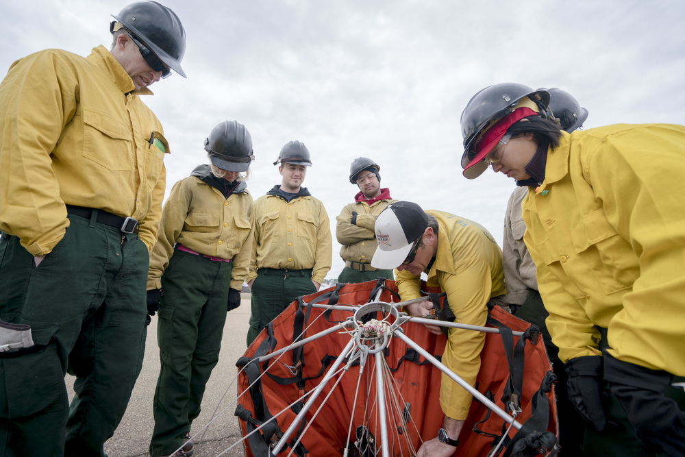 Jason Notz, right, show how to deploy a water bucket. Team Rubicon, with a partnership with the Bureau of Land Management, are being trained to become helicopter crewmembers for helitack teams to combat forest fires.  This is the first cohort to go to through this specialize training tailored for Team Rubicon volunteers.