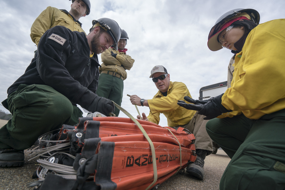 Jason Notz, center, show how to pack up a water bucket. Team Rubicon, with a partnership with the Bureau of Land Management, are being trained to become helicopter crewmembers for helitack teams to combat forest fires.  This is the first cohort to go to through this specialize training tailored for Team Rubicon volunteers.