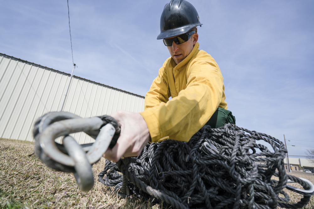 Team Rubicon member Travis Widder unravels a wrapped up cargo net. Team Rubicon, with a partnership with the Bureau of Land Management, are being trained to become helicopter crewmembers for helitack teams to combat forest fires.  This is the first cohort to go to through this specialize training tailored for Team Rubicon volunteers.