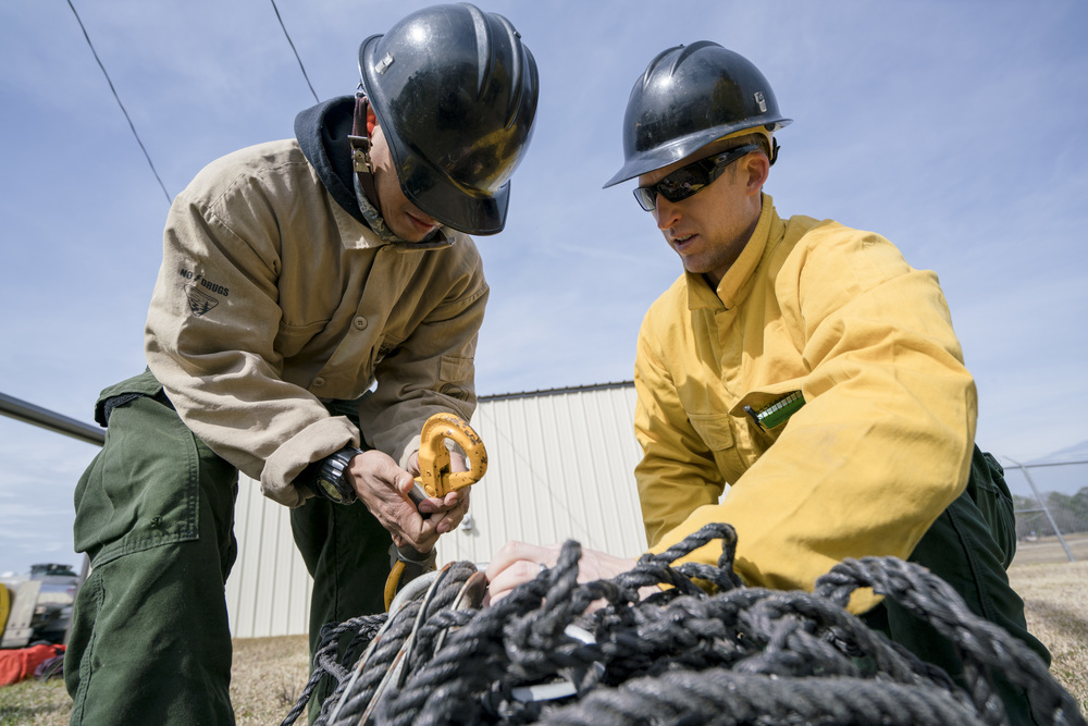 Team Rubicon members Robert Rose (left) and Travis Widder learn how a cargo net hook functions. Team Rubicon, with a partnership with the Bureau of Land Management, are being trained to become helicopter crewmembers for helitack teams to combat forest fires.  This is the first cohort to go to through this specialize training tailored for Team Rubicon volunteers.