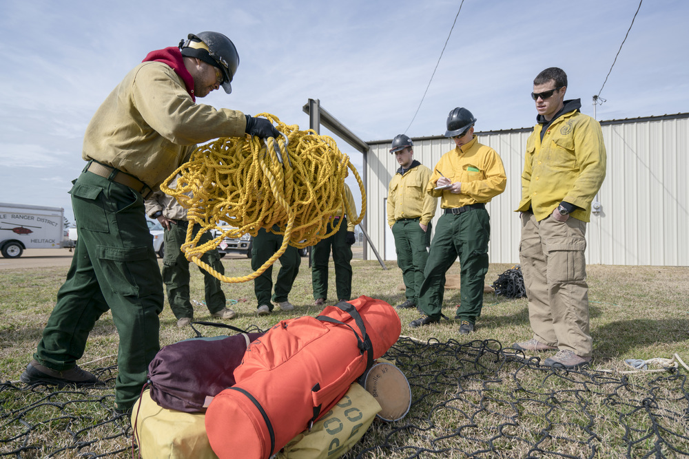 Team Rubicon wildland firefighters learn how to properly stow gear onto a cargo net. Team Rubicon, with a partnership with the Bureau of Land Management, are being trained to become helicopter crewmembers for helitack teams to combat forest fires.  This is the first cohort to go to through this specialize training tailored for Team Rubicon volunteers.