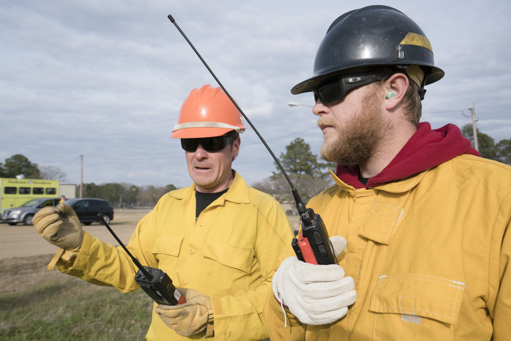 Team Rubicon member Chris Taylor, right, learns how to use proper radio communication to inform the pilot of cargo pickups and dropoff locations. Team Rubicon, with a partnership with the Bureau of Land Management, are being trained to become helicopter crewmembers for helitack teams to combat forest fires.  This is the first cohort to go to through this specialize training tailored for Team Rubicon volunteers.