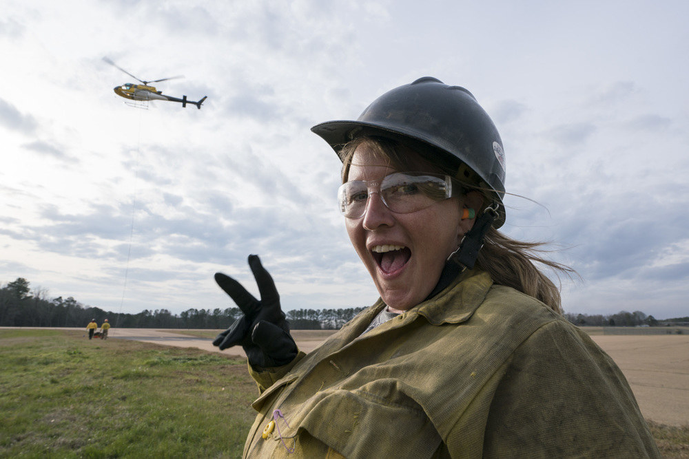 Team Rubicon members Anjy Wheeler poses for a photograph with flight operations behind her. Team Rubicon, with a partnership with the Bureau of Land Management, are being trained to become helicopter crewmembers for helitack teams to combat forest fires.  This is the first cohort to go to through this specialize training tailored for Team Rubicon volunteers.