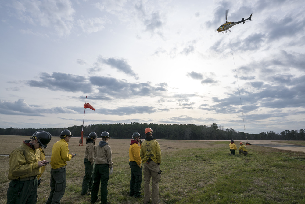 Team Rubicon wildland firefighters learn how to attach cargo to a hovering helicopter. Team Rubicon, with a partnership with the Bureau of Land Management, are being trained to become helicopter crewmembers for helitack teams to combat forest fires.  This is the first cohort to go to through this specialize training tailored for Team Rubicon volunteers.