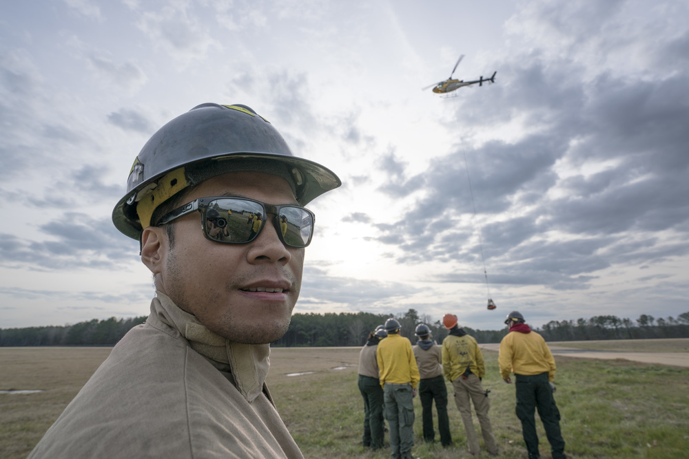 Team Rubicon members Charles Aquino poses for a photograph with flight operations behind him. Team Rubicon, with a partnership with the Bureau of Land Management, are being trained to become helicopter crewmembers for helitack teams to combat forest fires.  This is the first cohort to go to through this specialize training tailored for Team Rubicon volunteers.