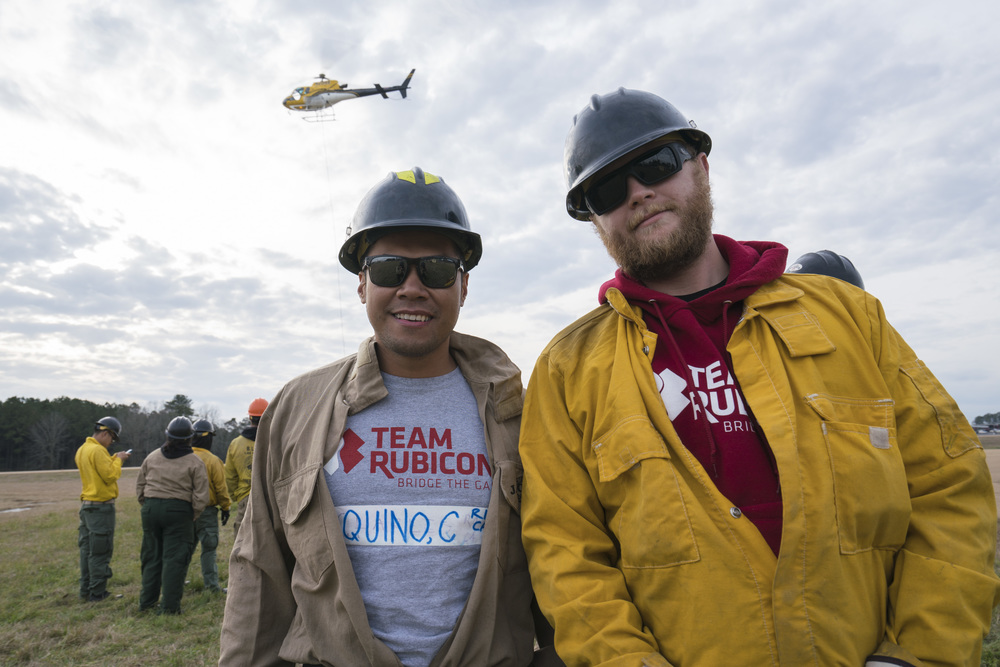 Team Rubicon members Charles Aquino (left) and Chris Taylor pose for a photograph with flight operations behind them. Team Rubicon, with a partnership with the Bureau of Land Management, are being trained to become helicopter crewmembers for helitack teams to combat forest fires.  This is the first cohort to go to through this specialize training tailored for Team Rubicon volunteers.