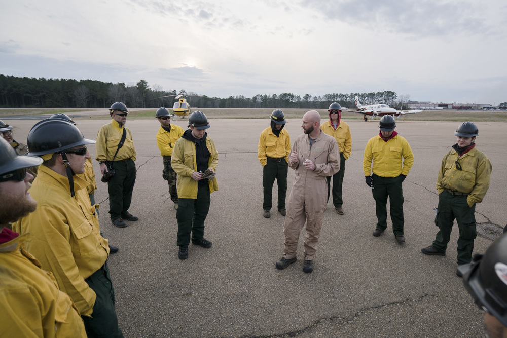 Pilot Preston Aro, center, talks to Team Rubicon wildland firefighters after finishing flight operations. Team Rubicon, with a partnership with the Bureau of Land Management, are being trained to become helicopter crewmembers for helitack teams to combat forest fires.  This is the first cohort to go to through this specialize training tailored for Team Rubicon volunteers.