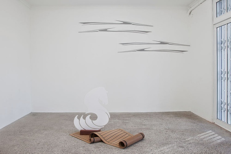Floor work: Broadening the horizons of your dreams (a discreet sense of luxury), 2014, laser cut vinyl applied to Perspex, custom made synthetic teak mat, Eco wood decking, 90 x 35 x 14cm.  Wall work: Water's edge, 2014, boat decals painted on wall, 3 x 2 metres.