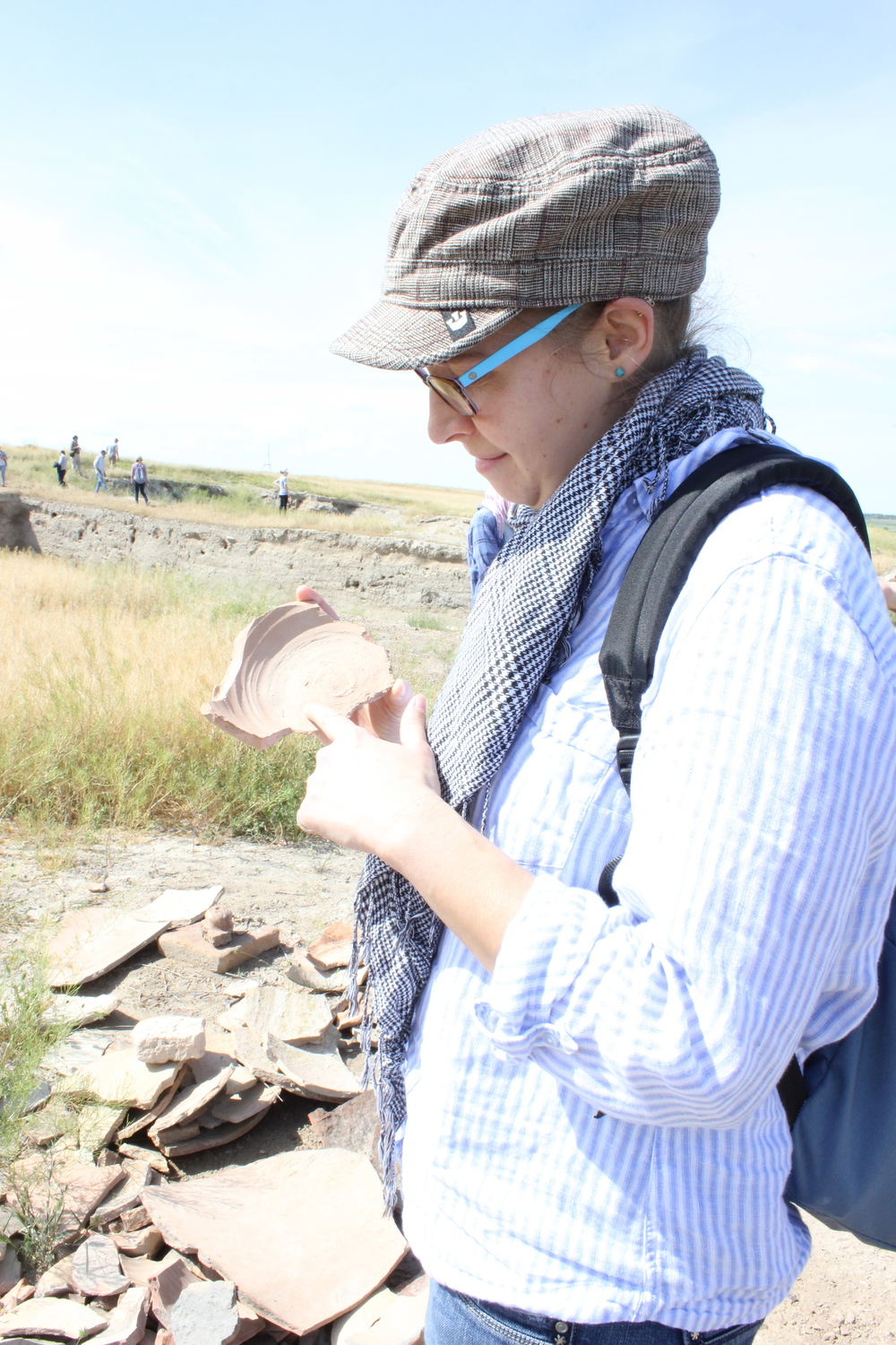 Natalie examining a piece of pottery sherd