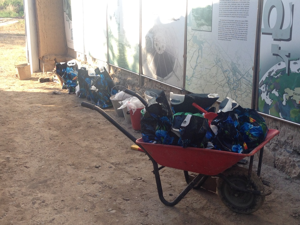 Line 'em up! Wheelbarrow and bags full of finds, ready for end of day processing!