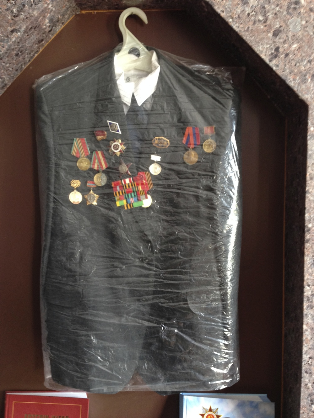 Suit jacket used as mounting for service medals.  Although the plastic covering may seem slightly obscuring for the viewer, its does mean it can be easily removed when staff want to show the medals up close.