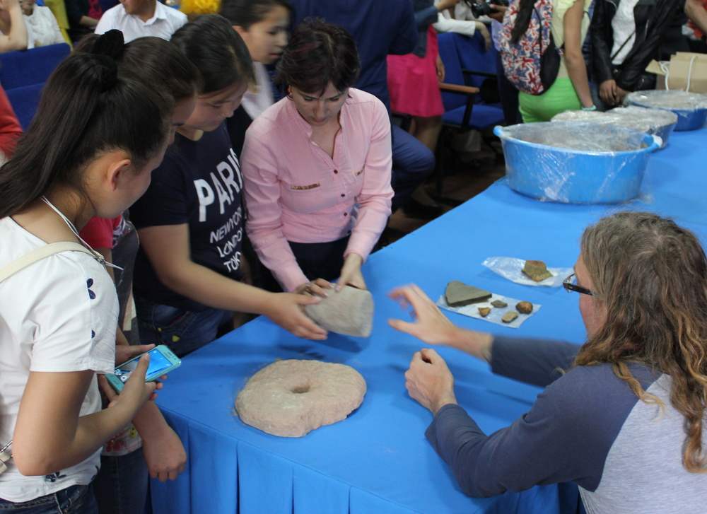 Giles showing students one half of a Quern stone (large circular object on the left) used for grinding, and a stone Pestle which is used to crush grains and explaining their historical uses.