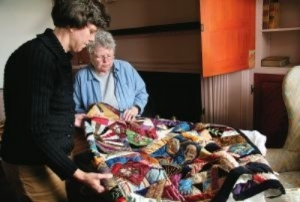 Image of former curator Gloria Comstock examining and assessing a 19th century Crazy Quilt.