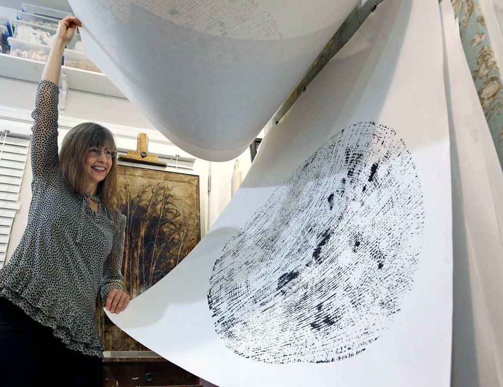 Dawn Flores shows a print of rings of a felled tree that was cut down on property behind her south Richmond home. She and three other artists are making pieces that reflect the beauty of the small forest.  Picture: Richmond Times Dispatch, Jan. 23, 2016