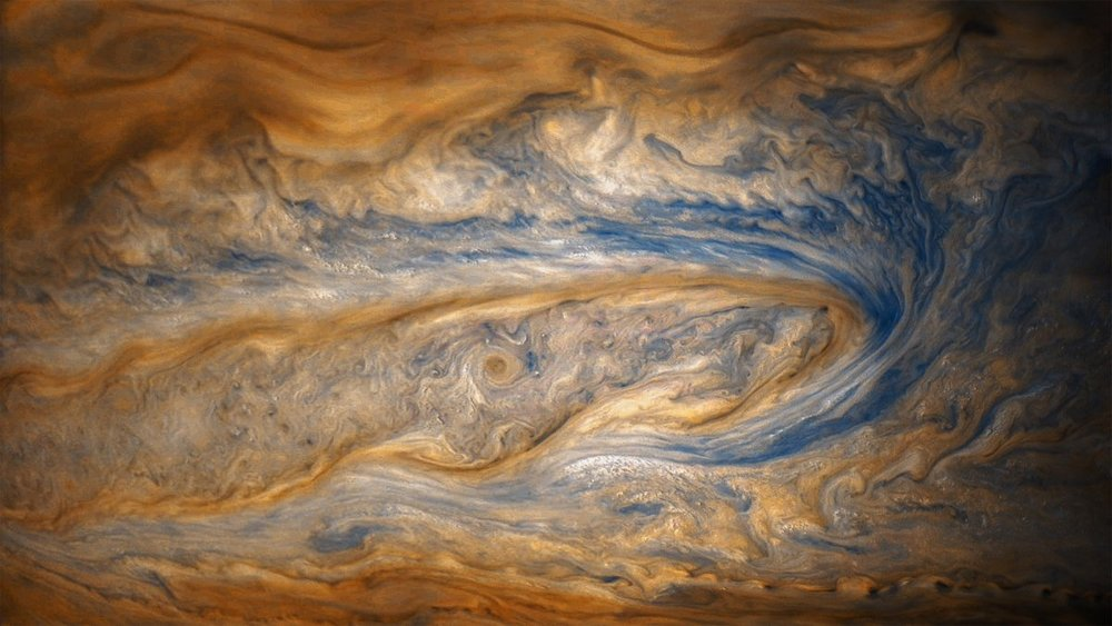 in-this-older-view-of-jupiter-from-junos-eighth-perijove-two-cloud-bands-battle-for-dominance--one-of-which-contains-a-swirling-storm-many-times-larger-than-a-hurricane-on-earth.jpg