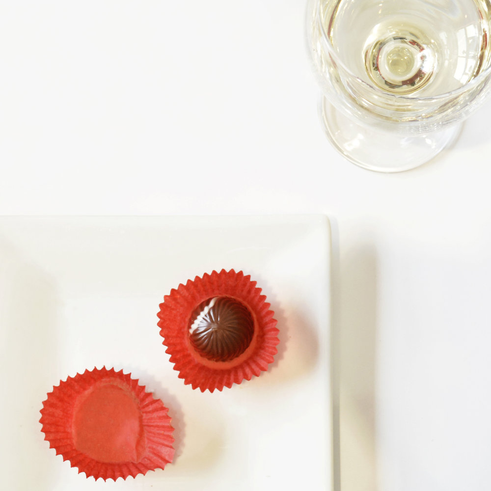 SPRING 2016 - wine and bonbon pairing   during my first few months at chuao, i was invite to join in on a wine and bonbon pairing to take some photos. this was one of my first photos taken at chuao. i love the use of white space and how your eye gets drawn right to the bonbon.