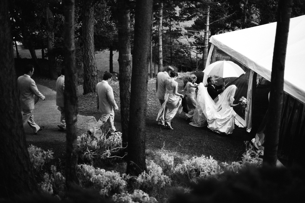 Couple and wedding party run to the tent after rain cuts their ceremony short at Rosario Resort on Orcas Island, WA