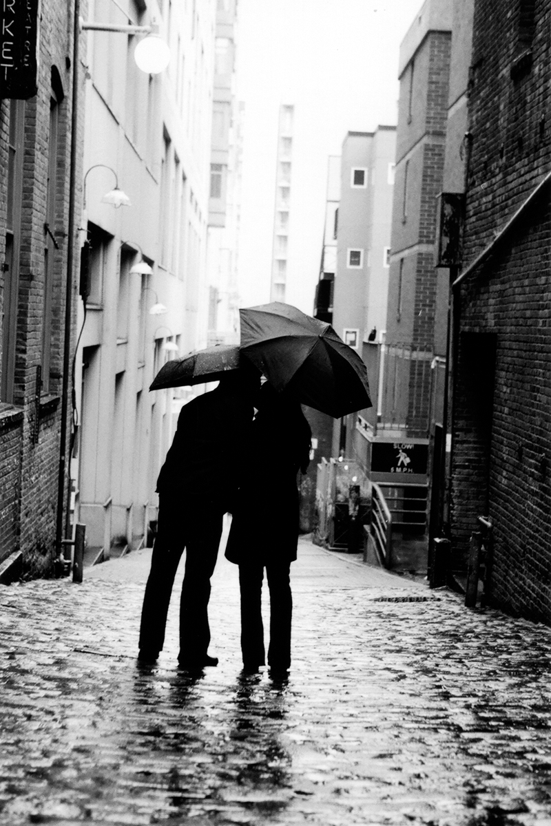 Engagement portrait at Post Alley in Seattle, WA during a rare summer rain