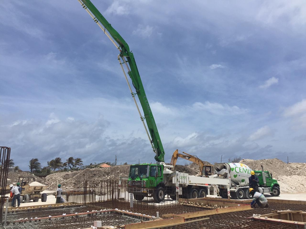 Boom pump pouring concrete to complete building foundation