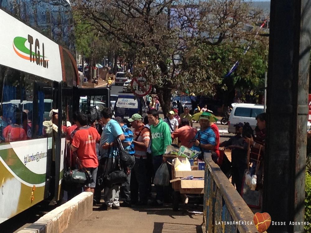 Paraguayos intentando vender cosas para bus brasileño