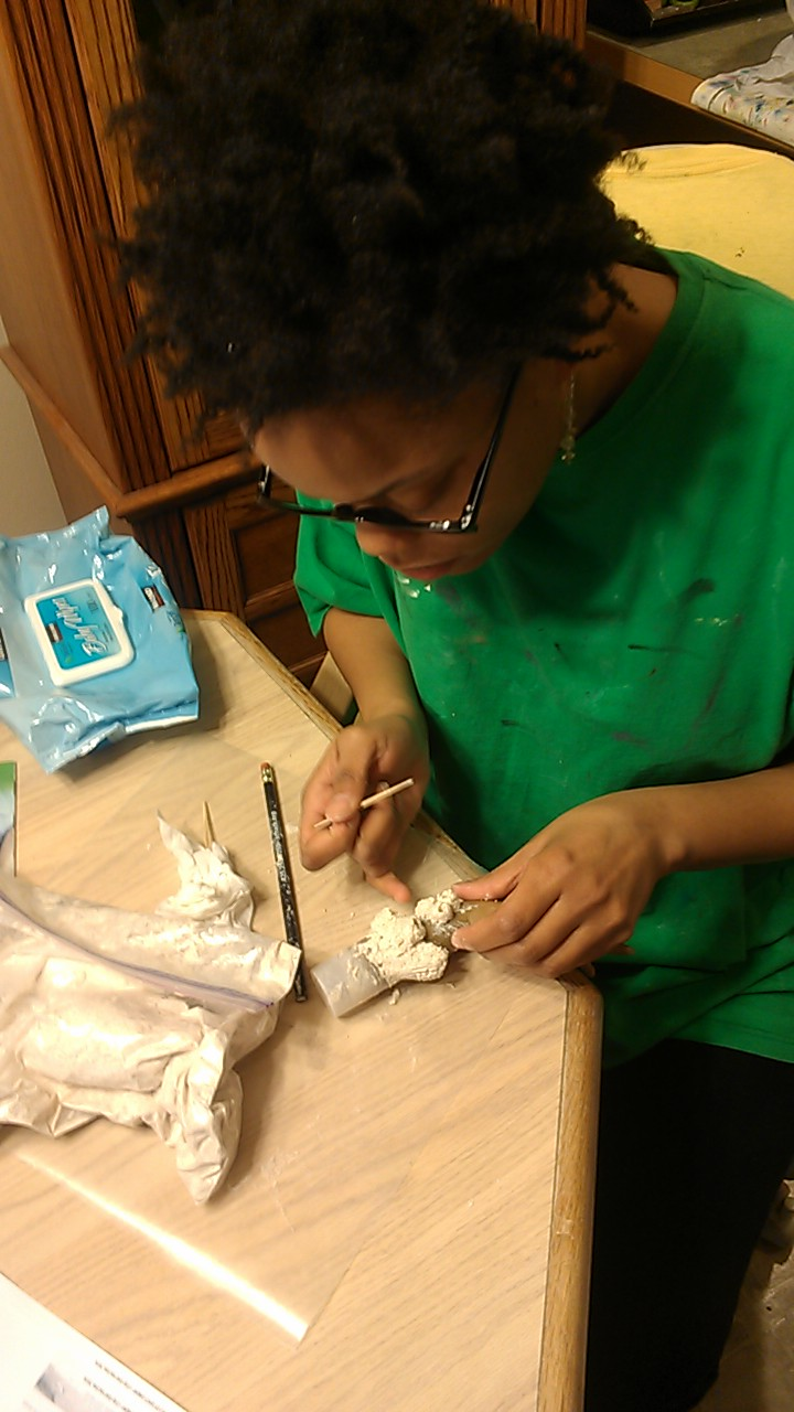 Action Shot of Lisa Myers Bulmash in green smock making paper mache barnacles