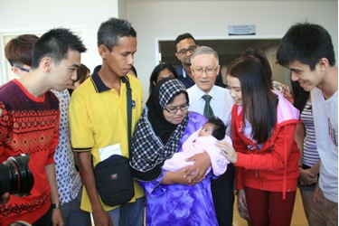 Prof Ho and the full-time students look on as the baby lies in her mum's arms