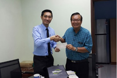 Adrian Siew hands over cheque to Pastor Alvin Tan