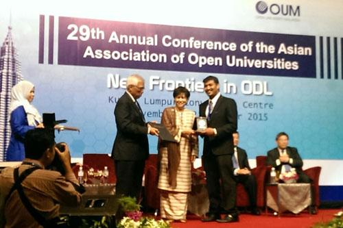 Dr Vighnarajah receiving his silver medal from Tun Jeanne Abdullah.
