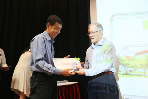Tan Pooi See receiving from Prof Ho.