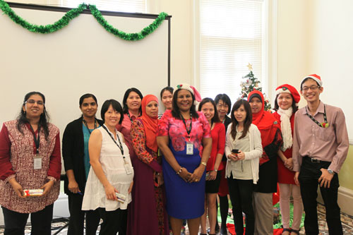 Gomathi (2nd from left) and her team pose with the organising committee (in Santa caps).