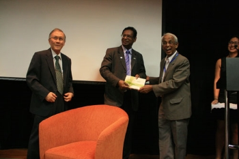 Tan Sri Emeritus Prof Gajaraj Dhanarajan, Convener of the Symposium, shows his appreciation to Mr Imran.