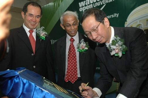 Dr Koh signs the plaque after the launch of the Regional Office. Looking on are Dato' Stephen Yeap and Prof Dhanarajan.