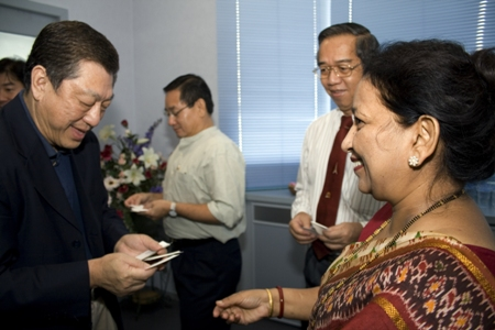 Dr Paul Chan exchanges name cards with WOU's Centre for Graduate Studies Director Prof Madhulika Kaushik.