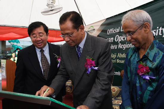 Abdul Ghani signing the plaque, flanked by Chia (left) and Prof Dhanarajan.