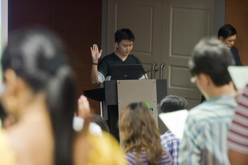 WOU web designer and new WOU student Johnathan Tan leads in the oath-taking,
