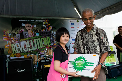 Grand Prize winner of the Post@Postcard Contest, Kim Hui Yu, receiving from Tan Sri Emeritus Prof Gajaraj Dhanarajan.