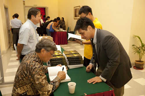 Andrew Sheng autographs his book.