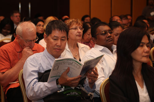 SST Dean Prof Tham Choy Yoong flips through the booklet. Beside him is senior lecturer Ishan.