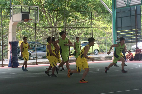WOU team (yellow jersey) in action on the basketball court.