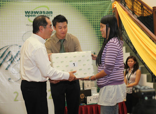 Dato' Seri Stephen Yeap presents the Encyclopaedia to Tan Hur Ting. At centre is Corporate Communications Manager Lim Yao-han.